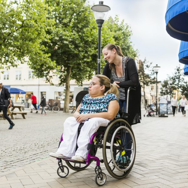 Assistant helping disabled woman in wheelchair move around city