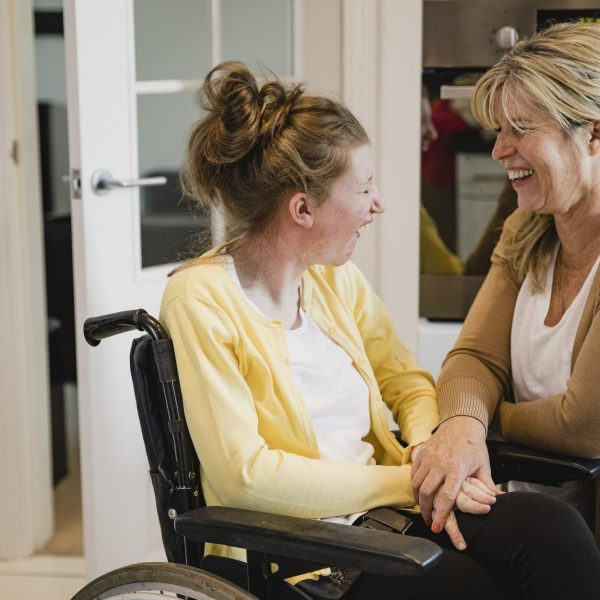 Mature mother is relaxing in the kitchen with her daughter who is in a wheelchair.